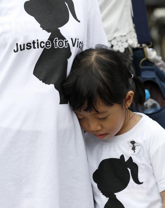6일 (현지시간) 미얀마 양곤 시내에서 '2살 여아 성폭행 사건' 항의 시위에 부모와 함께 참가한 어린이가 눈을 감고 있다. [EPA=연합뉴스]