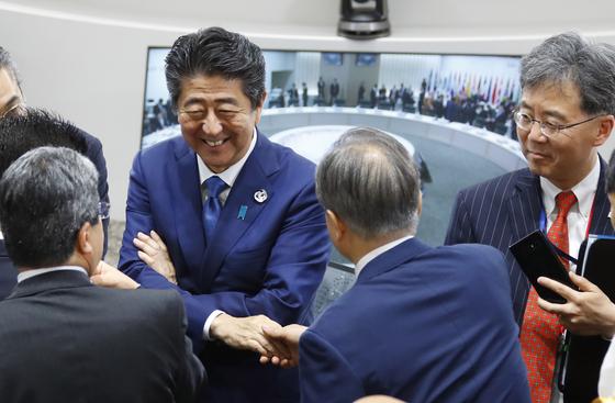 문재인 대통령이 6월 29일 오전 일본 오사카 인텍스 오사카에서 G20 정상회의 세션3 시작 전 일본 아베 총리와 인사하고 있다. 세션 직전 트럼프 대통령은 김정은 북한 국무위원장과의 판문점 회동 가능성을 트위터를 통해 발표했다. 연합뉴스