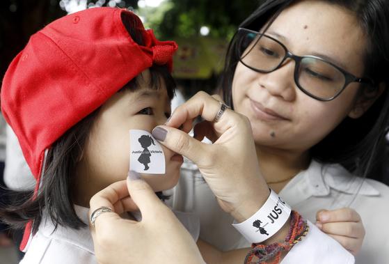 6일 (현지시간) 미얀마 양곤 시내에서 '2살 여아 성폭행 사건' 항의 시위에 부모와 함께 참가한 어린이가 얼굴에 '빅토리아에게 정의를' 스티커를 붙이고 있다. [EPA=연합뉴스]