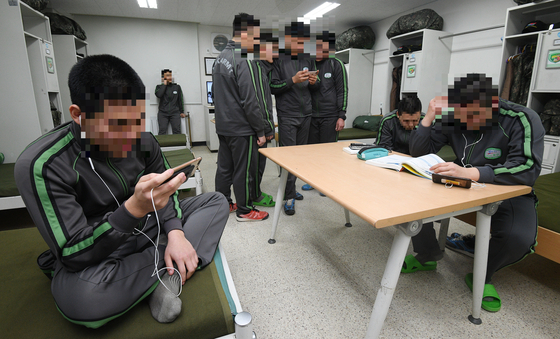 육군 수도기계화보병사단의 한 생활관에서 병사들이 휴대전화를 쓰는 모습. [사진공동취재단]