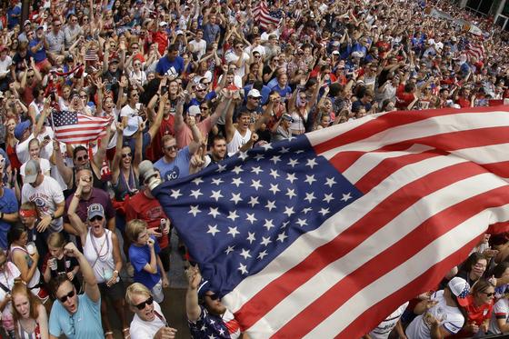 미국이 여자월드컵에서 우승하자 미국 캔자스시티에 마련된 팬존에서 경기를 지켜보던 미국 팬들이 성조기를 흔들며 환호하고 있다. [AP=연합뉴스]