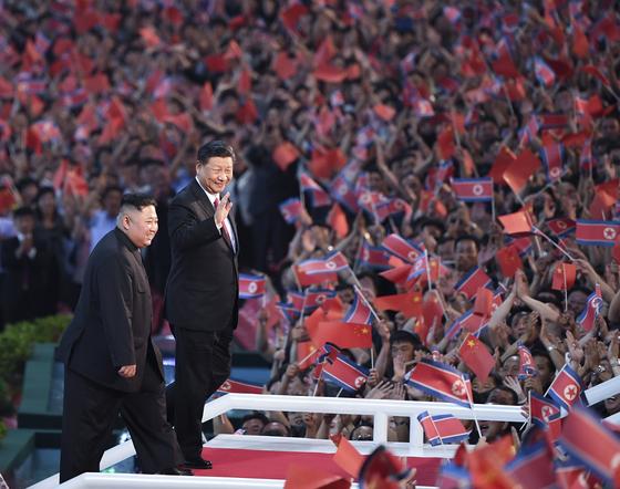 지난달 20일 북한 평양 능라도 51경기장에서 펼쳐진 대형 단체 공연이 끝나고 김정은 북한 국무위원장(왼쪽)과 시진핑 중국 국가주석(오른쪽)이 관객들의 환호에 답례하고 있다. [연합=신화]