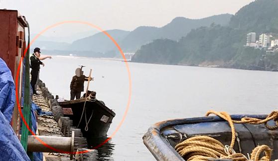 지난달 15일 오전 6시50분께 강원 삼척시 정라동 삼척항에 자력으로 입항한 북한 주민 4명을 해경이 조사하고 있다. [뉴시스]