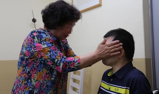 8일 오전 세종시의 한 사회복지시설에서 42년만에 아들과 상봉한 어머니가 두손으로 아들의 얼굴을 감싸며 눈물을 흘리고 있다. [사진 세종경찰서]