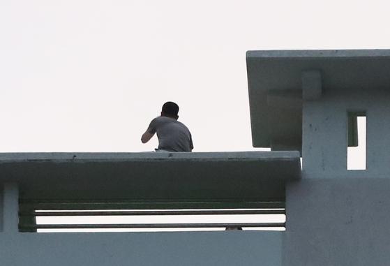 8일 오후 경남 거제시 옥포동 한 주상복합아파트 옥상에서 A씨(45)가 경찰과 대치하고 있다. [연합뉴스]