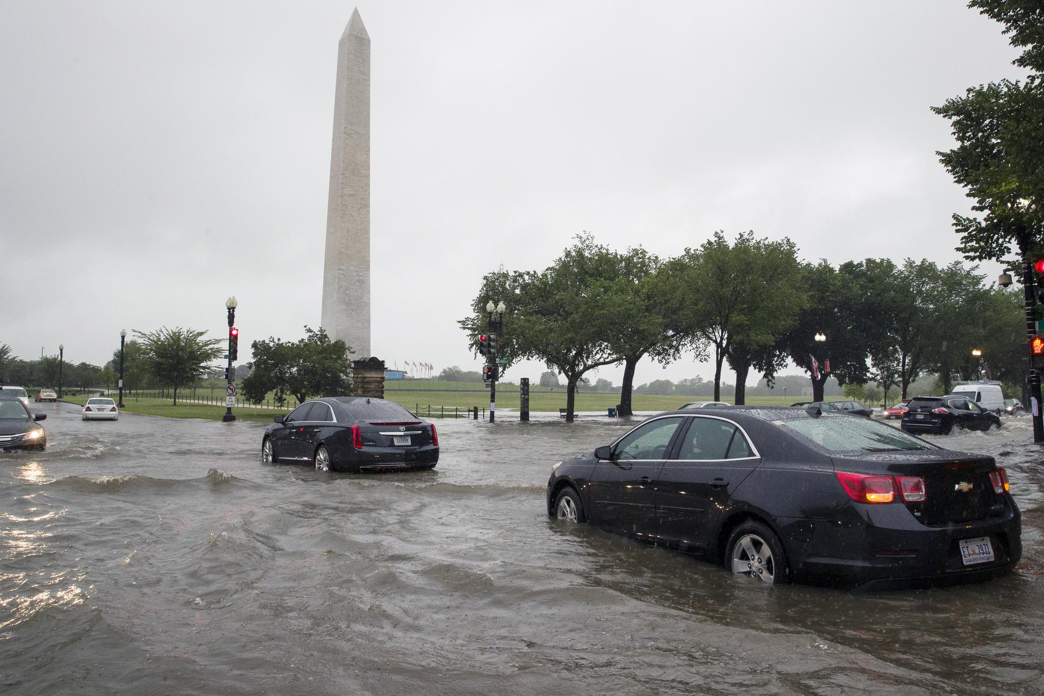 미국 워싱턴 DC 일대에 8일 오전(현지시간) 집중호우가 내렸다. 이날 워싱턴 기념탑 인근 도로가 물에 잠겨 차량이 서행하고 있다. [AP=연합뉴스]