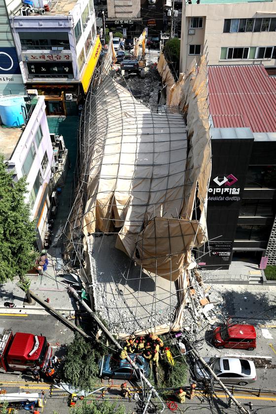 4일 오후 서울 서초구 신사역 인근의 5층 건물 외벽이 붕괴돼 소방대원들이 건물에 깔린 인명 구조작업을 하고 있다. [뉴스1]