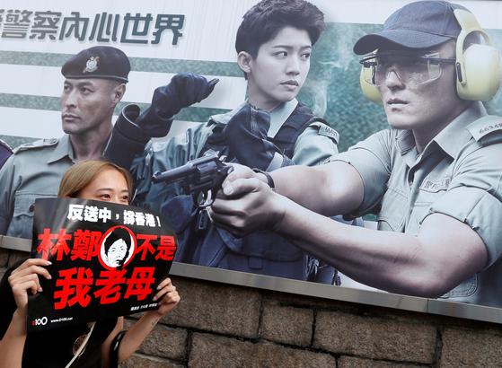 """홍콩 경찰 모집 포스터가 붙은 담장 아래서 홍콩의 한 여성이 """"캐리 람 행정장관은 더는 우리의 어머니가 아니다""""라는 문구가 적힌 플래카드를 들고 있다. [로이터=연합뉴스]"""