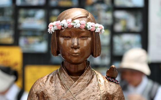 지난 5월 15일 서울 종로구 옛 일본대사관 앞에서 열린 '제1387차 일본군성노예제 문제해결을 위한 정기 수요시위'에서 소녀상의 머리에 화관이 씌워져 있다. [뉴스1]
