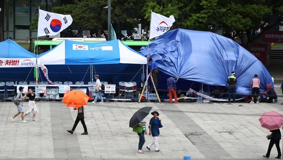 10일 오후 서울 광화문광장에서 우리공화당 관계자들이 천막에 방수포를 설치하고 있다. [연합뉴스]