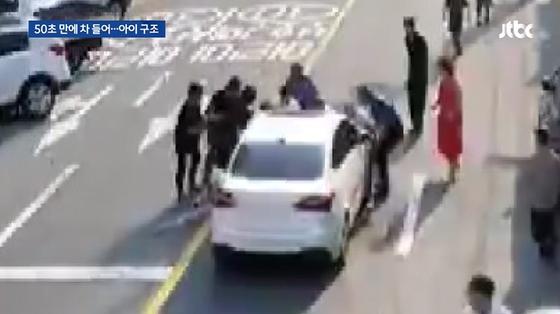 차량에 깔린 아이를 구하기 위해 모여든 시민들. [사진 JTBC]