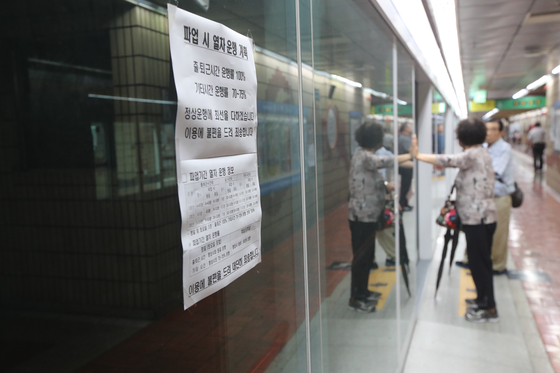 부산교통공사 노조가 파업을 한 10일 오전 한 지하철 역에 파업을 알리는 안내문이 적혀있고, 시민이 열차를 기다리고 있다. 송봉근 기자