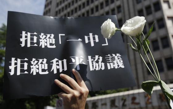 홍콩 시위가 한창이던 지난 6월 16일 대만 타이베이의 입법원 앞에서 벌어진 동조 시위에서 참가자가 ''하나의 중국을 거부하고 편화협정도 거정한다'는 구호를 들고 있다. [AP=연합뉴스]