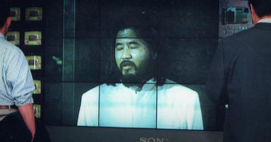 도쿄 시민들이 지난해 7월 사형을 집행한 아사하라 쇼코 옴진리교 교주에 대한 재판을 TV로 지켜보고 있다. [AFP=연합뉴스]