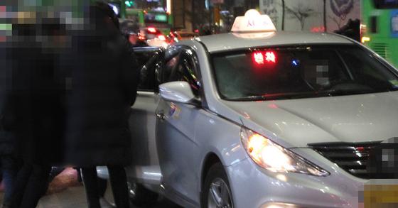 지난해 말 강남역 사거리에서 한 택시가 탑승하고자 하는 사람들과 실랑이를 하고 있는 모습. [중앙포토]