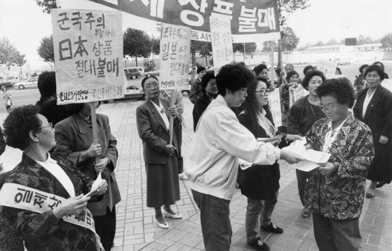 1992년 서울 잠실동 롯데백화점앞 광장에서 열린 일본제품 불매운동 집회 모습. 당시 이 백화점 10층에서 열린 '일본 니이가타 관광물산 전시회'를 규탄하기 위해 열렸다. 일본 상품 화형식을 한 뒤 시민들에게 관련 유인물을 나눠주고 있는 모습. [중앙포토]
