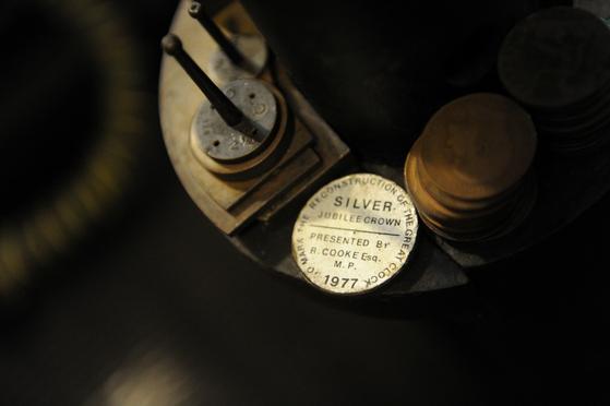 빅 벤 시계가 정확하게 유지할 수 있도록 동전들이 진자에 쌓여 있다. [로이터=연합뉴스]