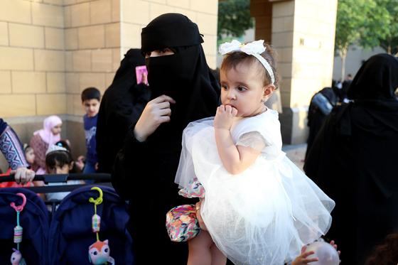 지난달 4일 사우디아라비아 수도 리야드의 한 모스크에서 한 사우디아라비아 여성이 아이를 앉은 채 서 있다. [리야드 EPA=연합뉴스]