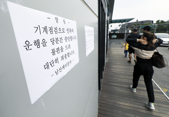 13일 서울 중구 남산케이블카 매표소에 운행 중단을 알리는 문구 앞으로 외국인 관광객들이 발길을 돌리고 있다. [뉴시스]