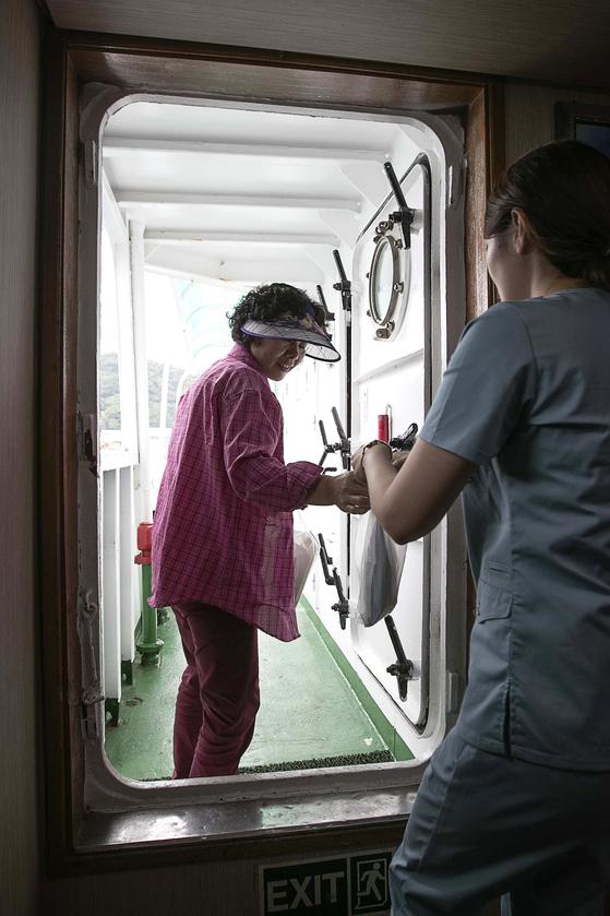 진료를 마친 섬 주민이 채미선 간호사가 건네주는 약을 받고 있다. 장진영 기자