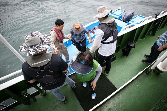 외연도 주민들이 소형 보트에서 병원선으로 옮겨타고 있다. 장진영 기자