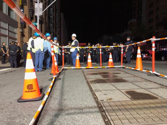 콘 에디슨 직원들이 13일(현지시간) 대규모 정전사태가 발생한 미국 뉴욕 시내에 바리케이드를 설치하고 서 있다. [로이터=연합뉴스]