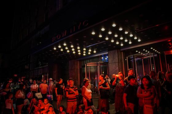 13일(현지시간) 대규모 정전사태가 발생한 미국 뉴욕에서 ROW NYC호텔 손님들이 건물 밖으로 대피해 있다. [로이터=연합뉴스]