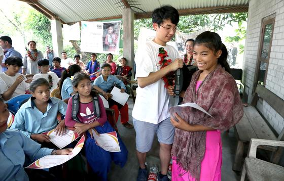 지난달 16일 네팔 치트완 틴도반학교에서 열린 장학금 행사에 참석한 장원영 학생이 아지나 체팡(오른쪽)에게 장학증서와 책가방을 선물하고 있다. 최승식 기자