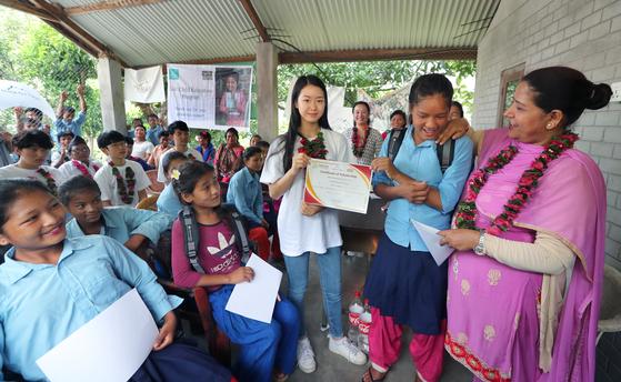 16일 헤퍼 장학금수여식이 열린 네팔 치트완 틴도반학교에 임수빈 학생이 네팔 여학생에게 장학금을 전달한 후 기념사진을 찍고 있다. 최승식 기자