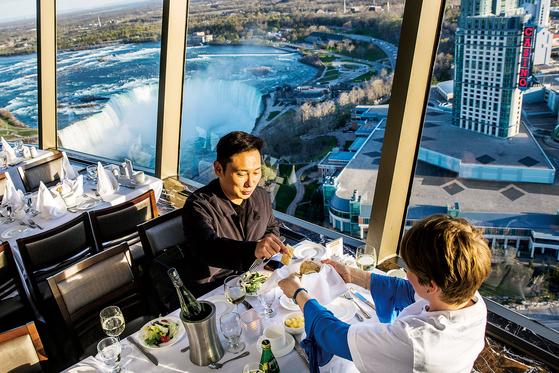 개그맨 이승윤이 스카일런 타워 전망대 레스토랑에서 식사를 하고 있다. 뒤편으로 나이아가라 폭포가 보인다. [사진 론리플래닛]