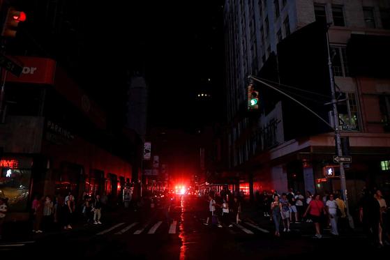 시민들이 13일(현지시간) 미국 뉴욕에서 발생한 대규모 정전으로 어둠에 묻히 맨해튼 거리를 걸어가고 있다.[AFP=연합뉴스]