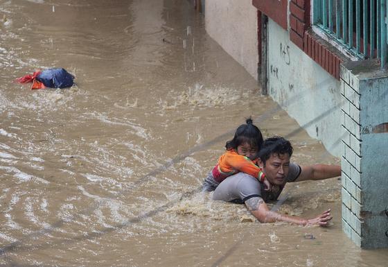 12일 (현지시간) 네팔 카트만두에서 폭우가 쏟아지자 한 남성이 딸을 데리고 침수 지역을 탈출하고 있다. [EPA=연합뉴스]