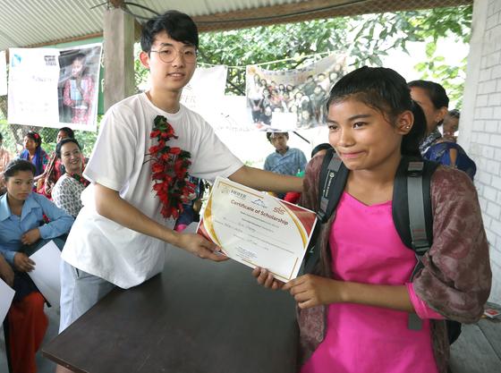 16일 헤퍼 장학금수여식이 열린 네팔 치트완 틴도반학교에 장원영 학생이 아지나 체팡에게 장학금 증서를 전달하며 기념사진을 찍고 있다. 최승식 기자