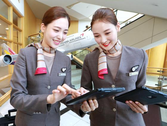 서울시 강서구 오쇠동 아시아나항공 본사에서 아시아나항공 캐빈승무원들이 새롭게 지급받은 태블릿 PC를 통해 스마트워크 플랫폼인 A-tab을 통해 스케줄을 확인하고 있다. [사진 아시아나항공]