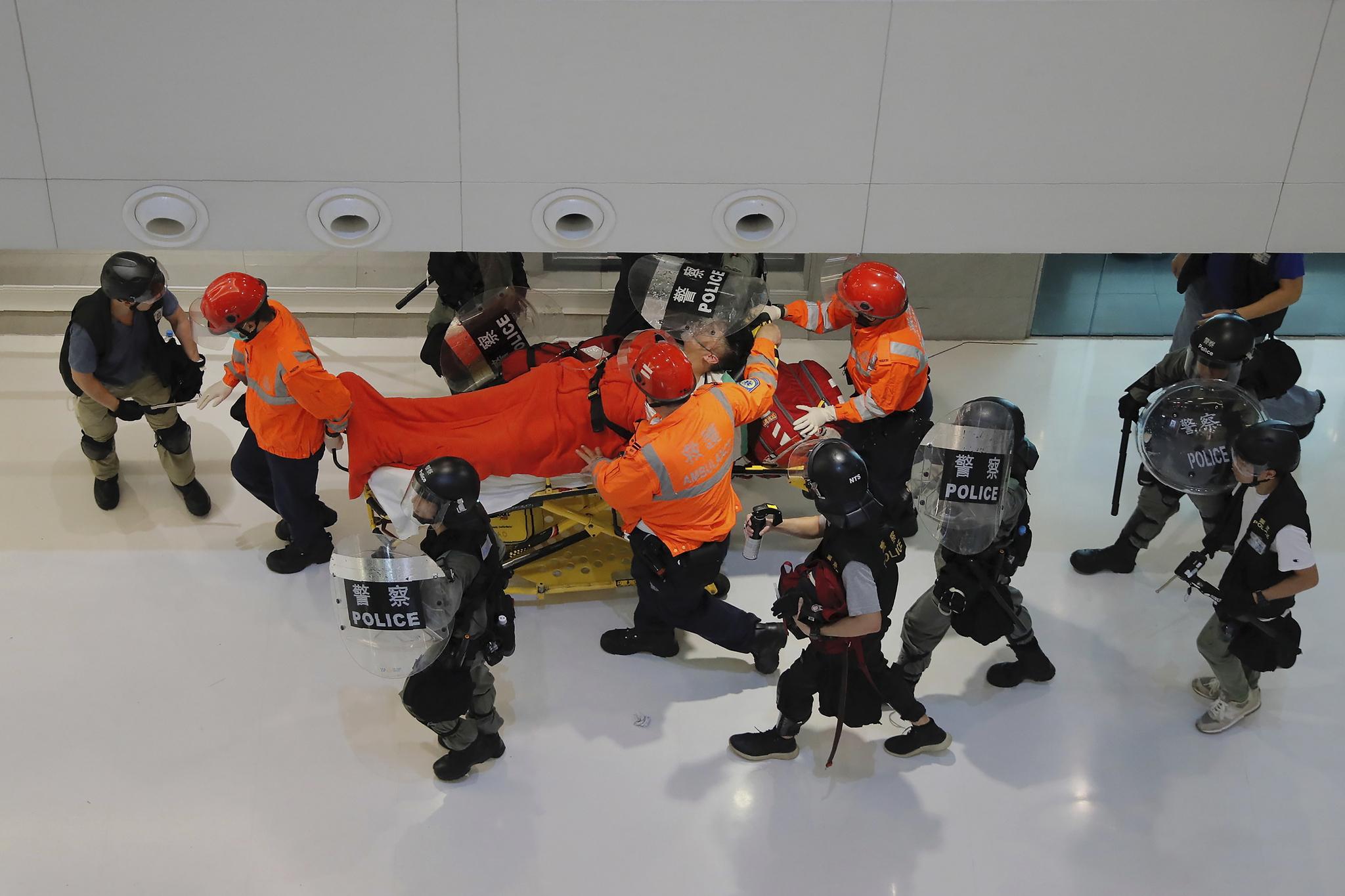 경찰과 시위대의 충돌로 발생한 부상자를 경찰들이 이송하고 있다. [AP=연합뉴스]