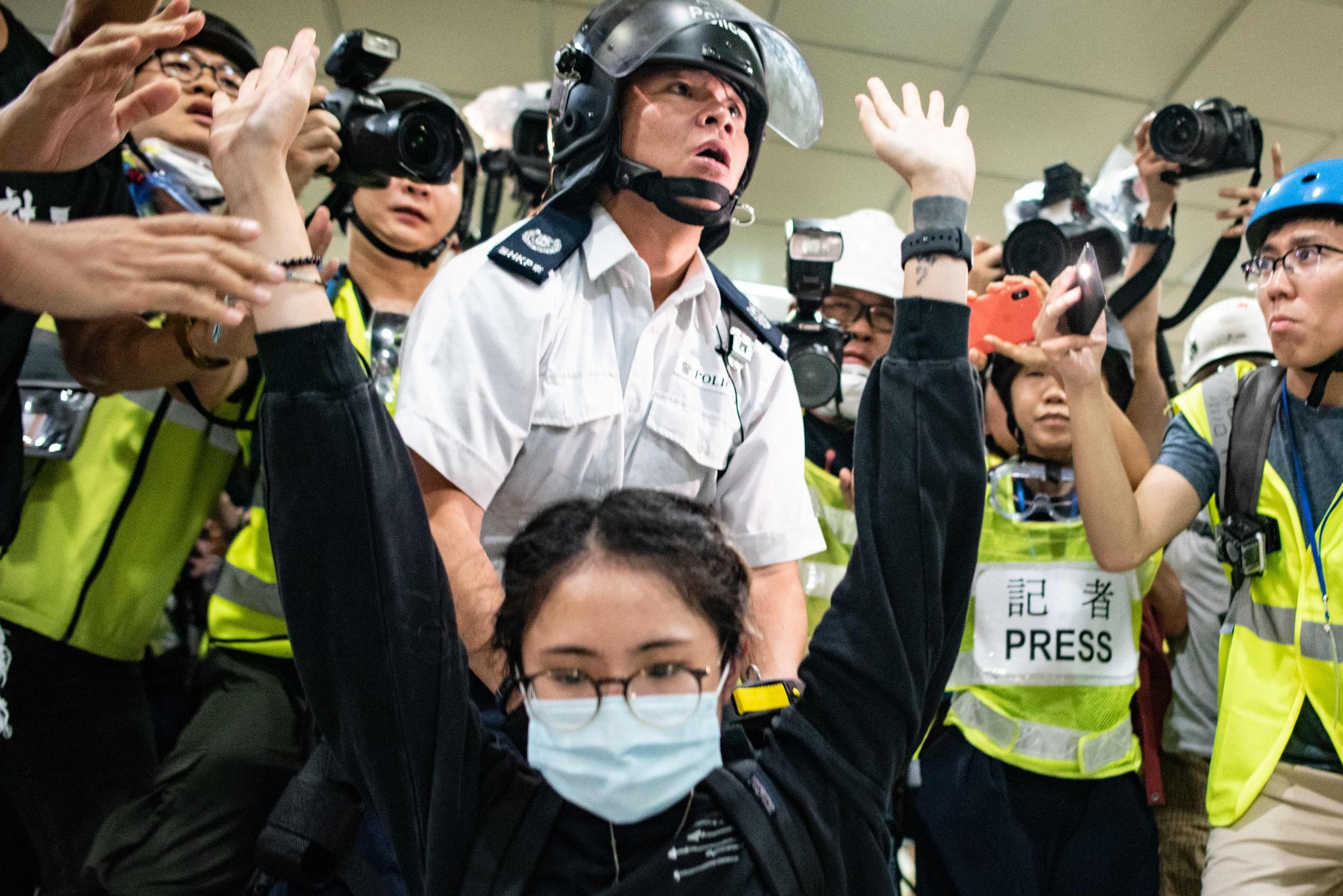 이날 한 여성 시위자가 경찰에 붙잡혀 무릎을 꿇고 두손을 들고 있다. [AP=연합뉴스]