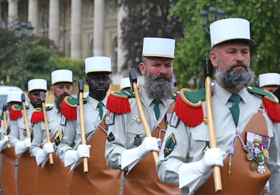 프랑스 육군 외인부대원들이 14일 파리 샹젤리제 거리를 행진하고 있다. 외인부대원들이 부대의 상징인 도끼를 들고 있다. [UPI=연합뉴스]