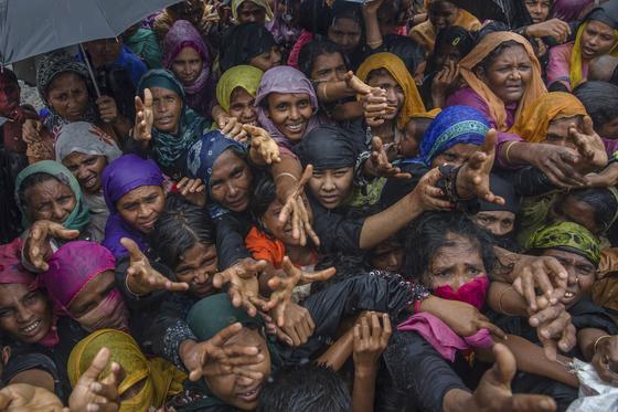 미얀마의 박해를 피해 방글라데시 발루칼리 난민 캠프에 거주 중인 로힝야족 여성들이 2017년 9월 17일 국제 구호단체의 구호품을 받기 위해 손을 벌리고 있다. [AP=연합뉴스]