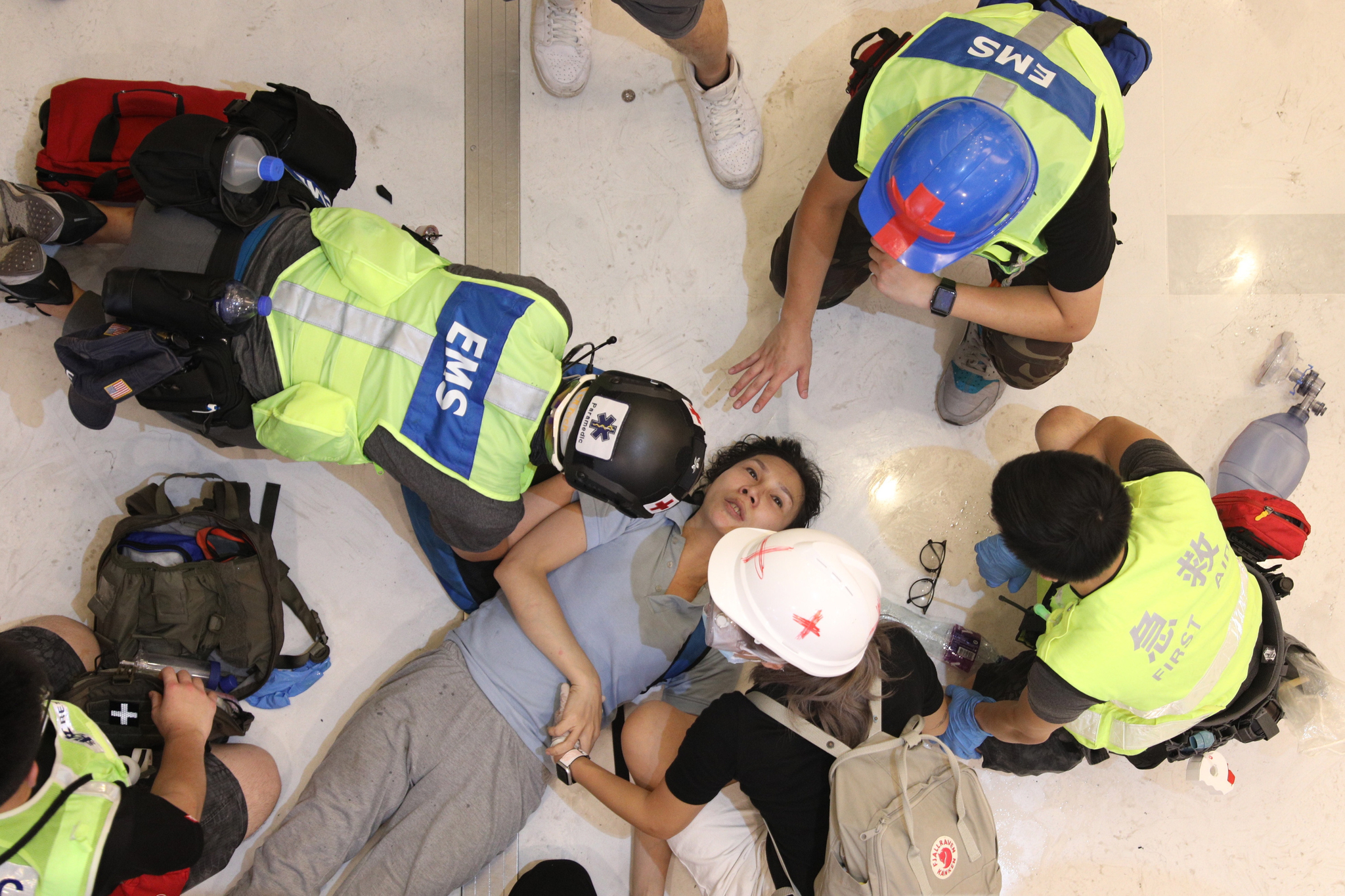 이날 부상을 당한 여성 시위자가 쇼핑몰 바닥에 들어누워 응급요원들에게 치료를 받고 있다. [EPA=연합뉴스]