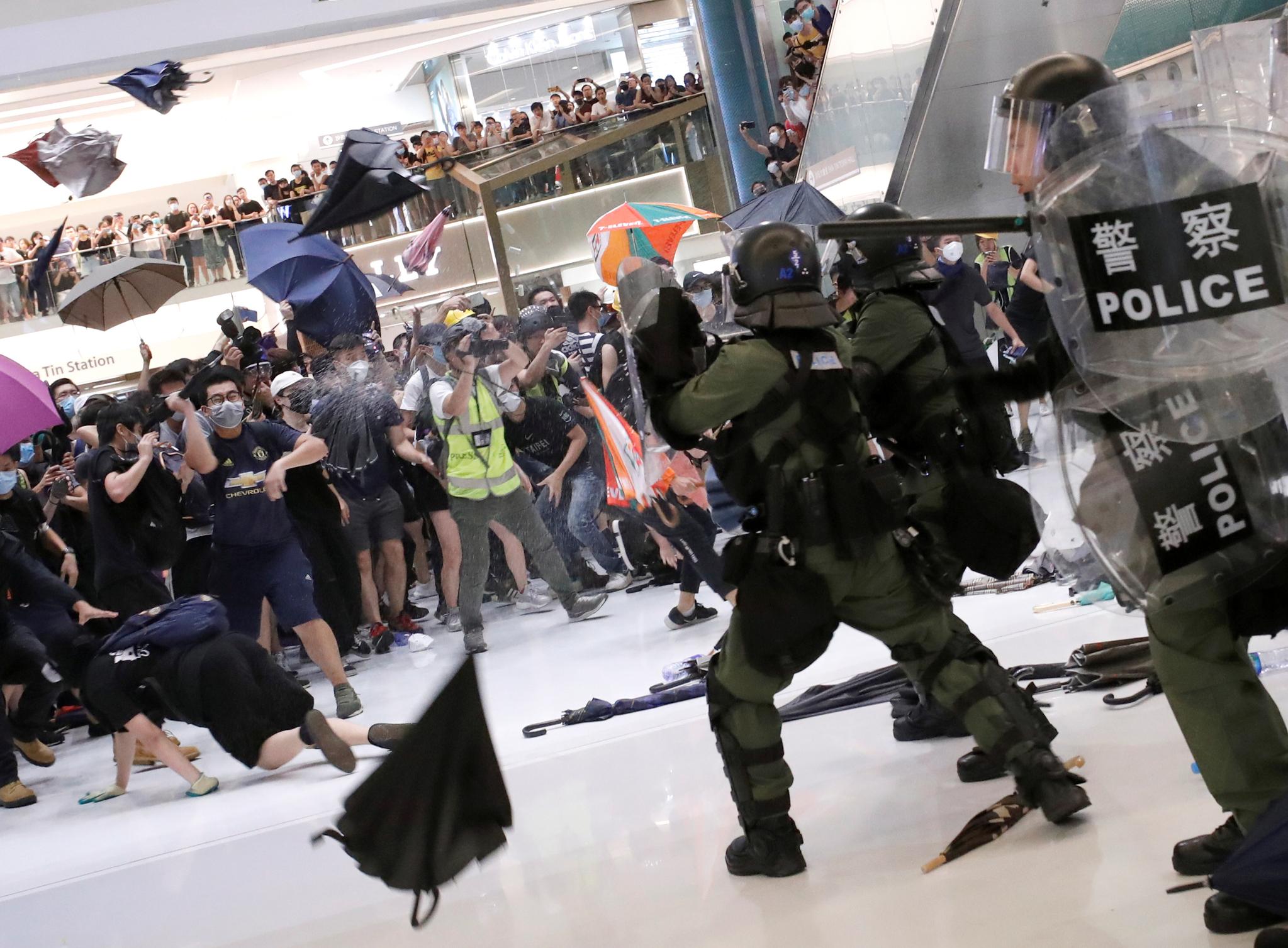 경찰과 시위대간의 격렬한 충돌이 발생한 14일(현지시간) 홍콩 뉴타운플라자에서 시위대들이 경찰을 향해 우산을 던지며 대치하고 있다. [AP=연합뉴스]
