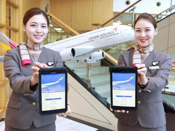 서울시 강서구 오쇠동 아시아나항공 본사에서 아시아나항공 캐빈승무원들이 새롭게 지급받은 태블릿 PC를 들어보이고 있다. [사진 아시아나항공]