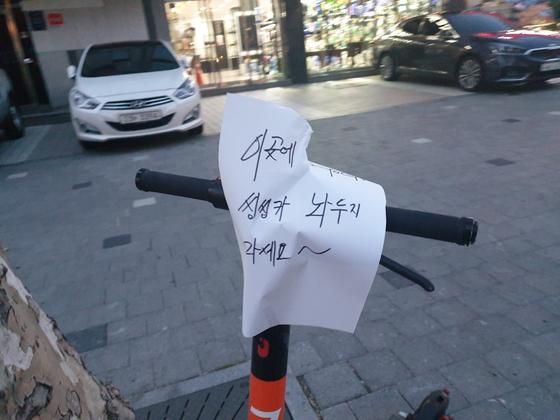 서울 강남의 한 길거리에 아무렇게나 방치된 공유 전동 킥보드. '이곳에 씽씽카 놔두지 마세요'란 경고 문구를 지나던 주민이 붙여 놓았다. [독자 제공]