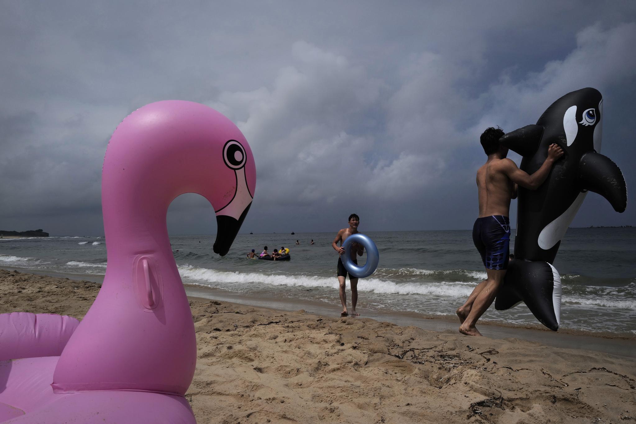 14일 북한 주민들이 강원도 통천 시중호 해수욕장에서 물놀이 기구를 가지고 피서를 즐기고 있다. [AP=연합뉴스]