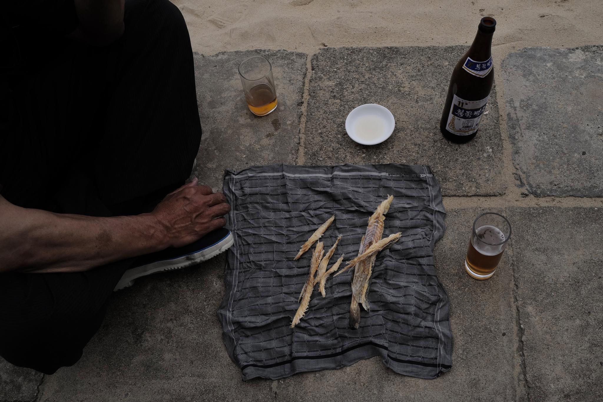 시중호 해수욕장의 맥주 한잔. 명태포를 안주로 맥주를 즐기고 있다. [AP=연합뉴스]
