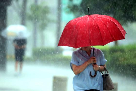소나기가 내리는 15일 오후 서울 강남구 학동역 인근 거리에서 시민들이 우산을 쓰고 걷고 있다. [뉴시스]