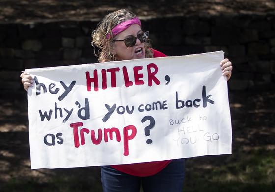 """도널드 트럼프 미국 대통령이 14일 민주당 여성의원들에 """"당신네 나라로 돌아가라""""는 트윗을 하자 한 여성 시위대가 버지니아 트럼프 내셔널 골프클럽 앞에서 대통령의 차량행렬을 향해 """"헤이 히틀러, 왜 트럼프로 환생해 돌아왔냐""""고 비난하는 글을 들고 있다.[EPA=연합뉴스]"""