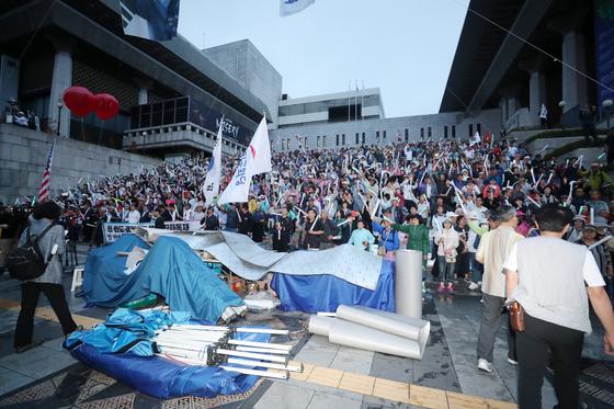 우리공화당 당원과 지지자들이 16일 오전 서울 세종문화회관 앞 계단에서 광화문광장에 설치됐던 천막을 자진 철거 후 구호를 외치고 있다. [뉴스1]