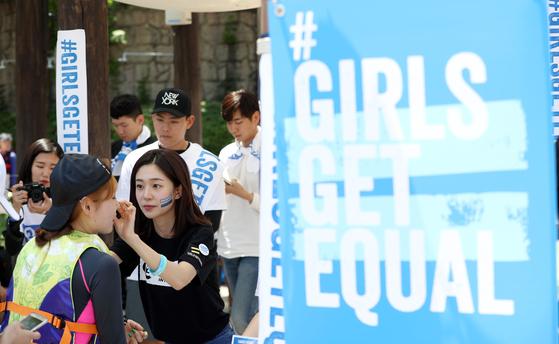 지난 6일 경기도 용인 에버랜드 캐리비안베이에서 열린 '걸스 겟 이퀄'(소녀는 동등한 권리를 갖는다는 뜻) 캠페인 행사.. 배우 백진희가 동등함을 상징하는 '등호' 표시 스티커를 시민 얼굴에 붙이고 있다. 우상조 기자