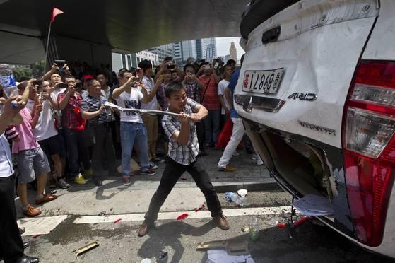 일본과 중국이 센카쿠 열도를 둘러싸고 대립이 한창이던 2012년 중국 선전에서 반일 시위대가 일본 자동차 회사 혼다가 만든 경찰차를 부수고 있다. [로이터]