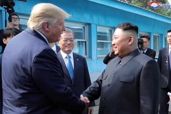 도널드 트럼프 미국 대통령과 김정은 북한 국무위원장이 지난달 30일 오후 판문점에서 악수하고 있다. 문재인 대통령이 이를 바라보고 있다. [연합뉴스]